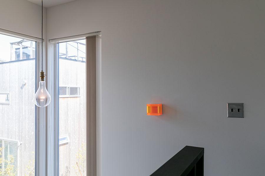 ドイツのアーティスト、レギーネ・シューマンの《カラーミラー・サンオレンジ・トーキョウ》。「スイッチと並べて飾りました。ブラックライトを当てるととても美しいです」。タグチファインアートで購入。