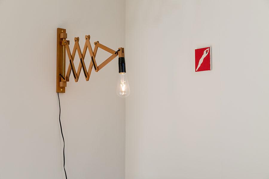 赤い小さな作品は、灰方るり。「狩野岳朗さんの抽象的な作品の隣に飾るなら、具象的なものがいいなと考えてました」。ライトは後藤睦の作品。