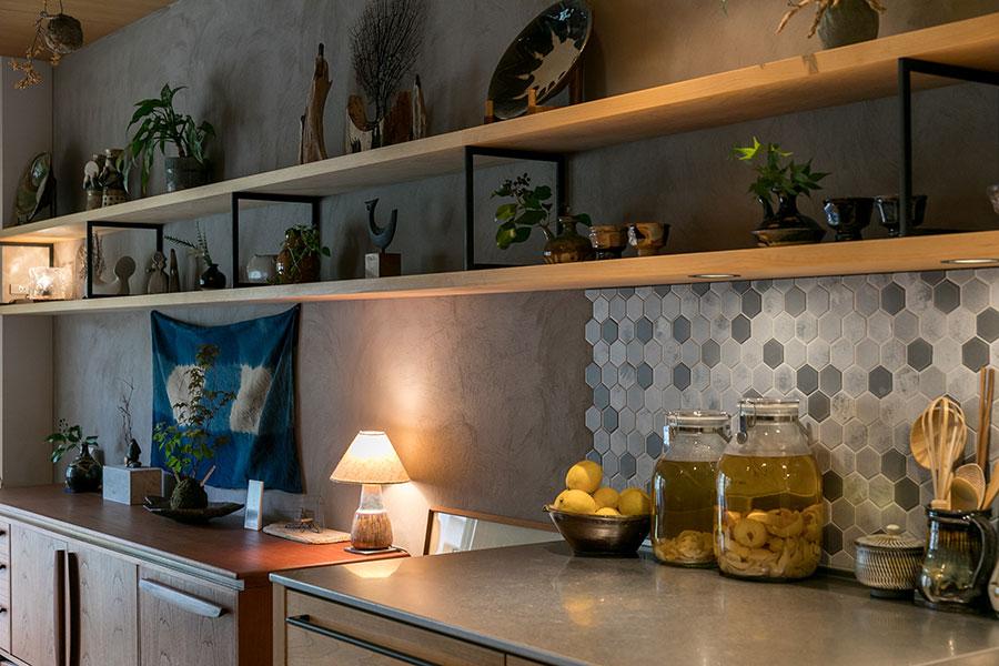 キッチンからリビングまで壁に沿って飾り棚が伸びる。スクエアな棚受けはスチール製。
