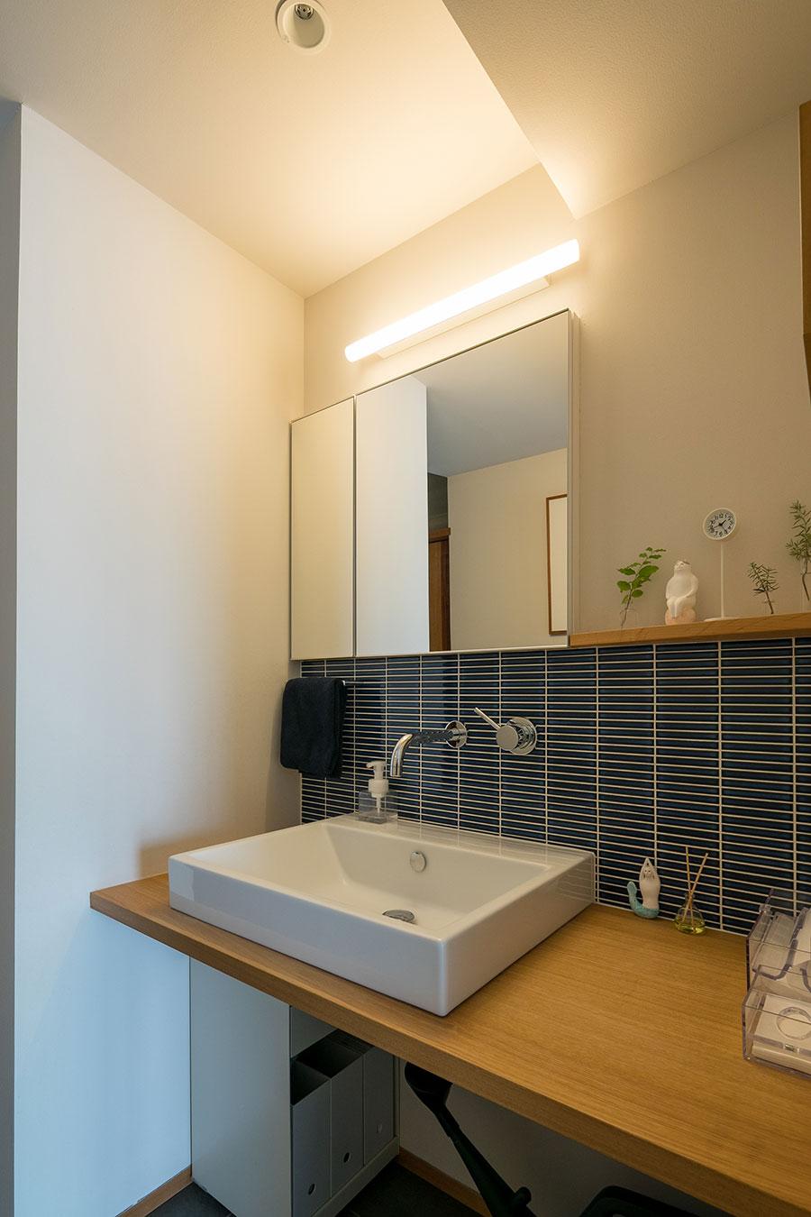 洗面所には清潔感のある紺色のタイル。壁付の蛇口は掃除もラク。