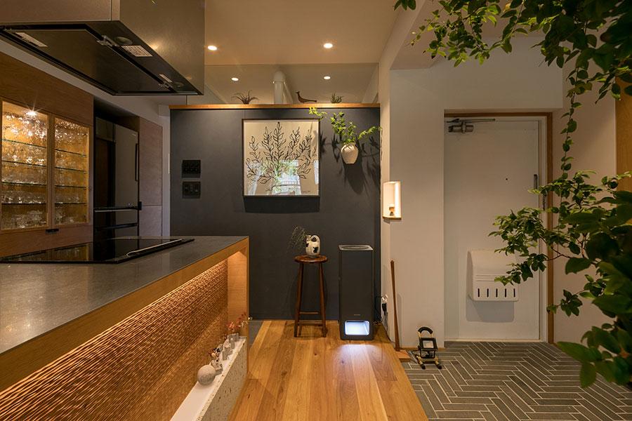 正面の濃紺の壁の向こうが水回りとプライベートスペース。壁の上はガラスになっていて、奥へとつながりを感じさせる。