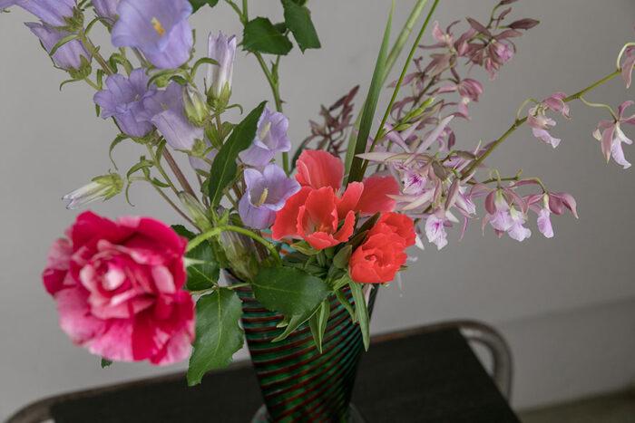 バラの葉で花瓶の口元にボリュームを出す。花材はバラ、ゴデチア、カンパニュラ、イキシア、エンクシリア、アストロメリア、
