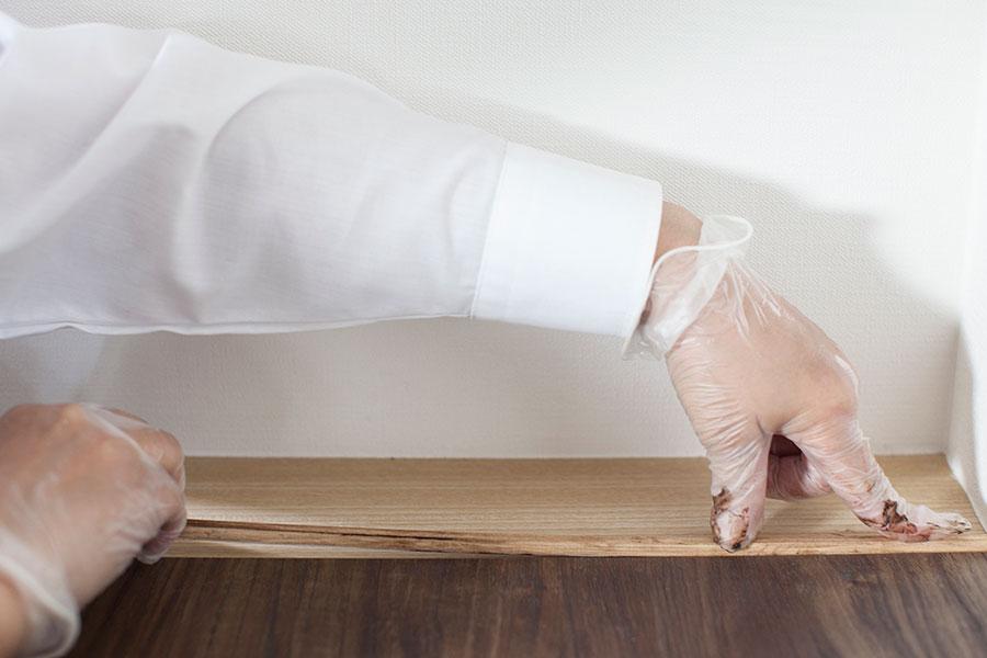 ワックスを塗った工作材の裏側に両面テープを貼り、靴箱との際に天板から側面まで貼り付ける。貼ったら上から圧着し、ミニビスや隠し釘などでしっかり固定する。