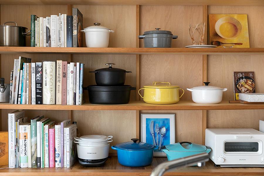 夫の提案で設置した棚。料理本や鍋が多いことを逆手に取り、見せる収納棚にした。鍋はブックエンドの役割も持つ。中には50年代に販売されたビンテージものの鍋もある。