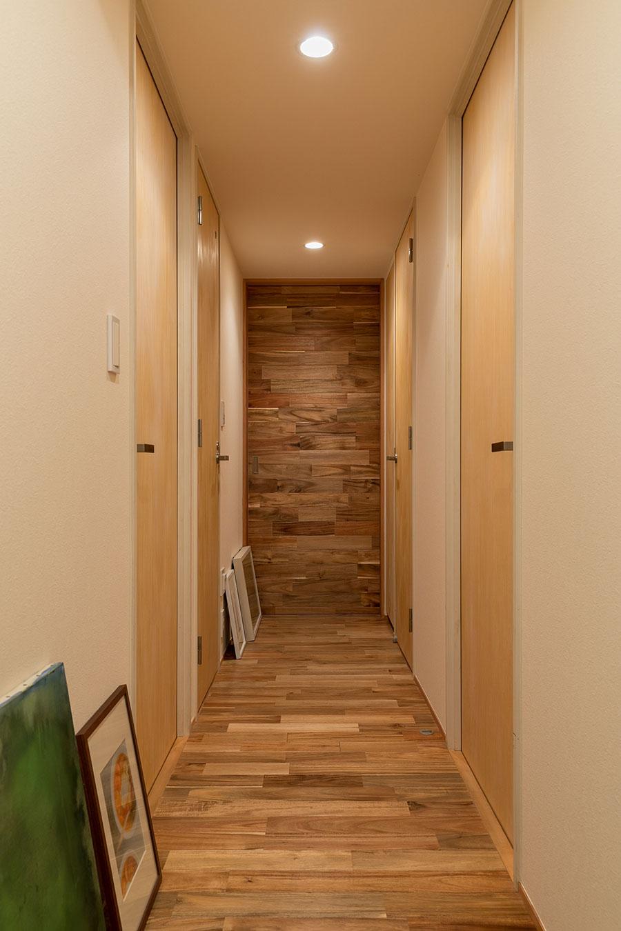 玄関からリビング・ダイニングに続く廊下。引き戸も床と同じアカシア材で、空間に統一感がある。「ギャラリーのようになった」と絵が好きな有賀さんお気に入りの場所の1つ。