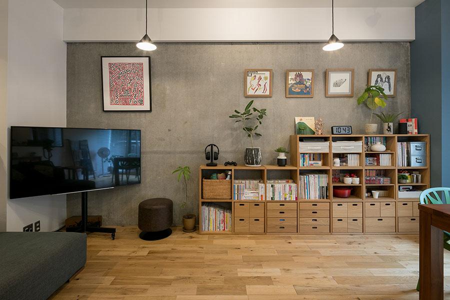 リビングの壁面は、以前の壁紙を剥がした躯体をそのまま生かしている。無印良品のスタッキングチェストを組み合わせて本や雑貨を収納している。