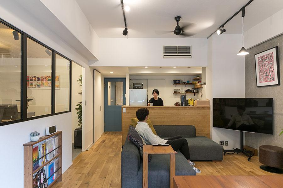 キッチンは、リビングにいる人と会話ができるようにオープンなタイプにリノベーションした。2人でゆったりと座れるソファは、新居に合わせて御徒町のRignaで購入したもの。
