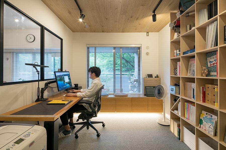 ワークスペースは、床をタイルカーペット張りとして、他の部屋と変化をつけている。奥の造り付けのベンチは収納もかねる。