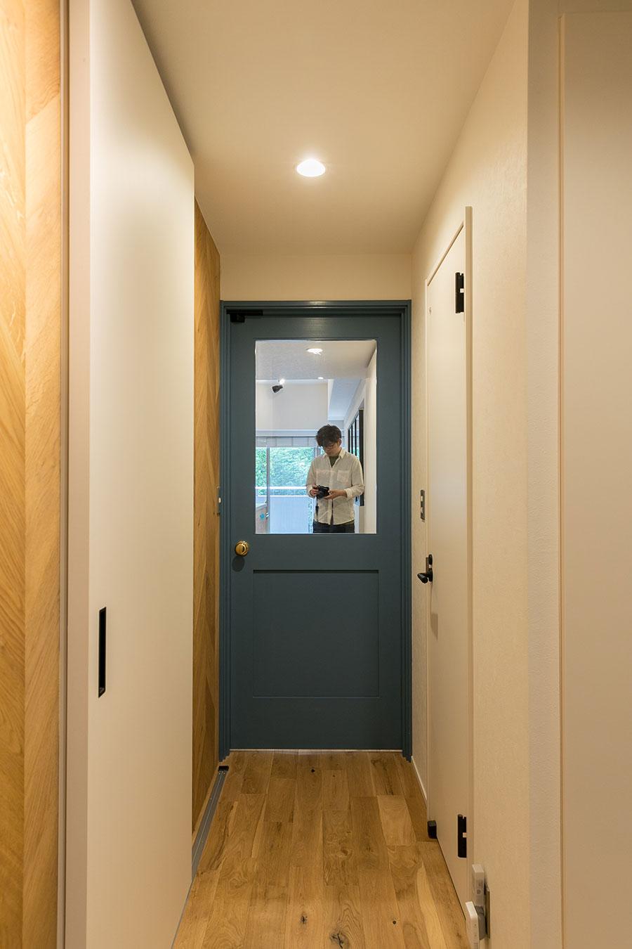 玄関の廊下からリビング側を見る。扉はくすんだブルーに塗装した。