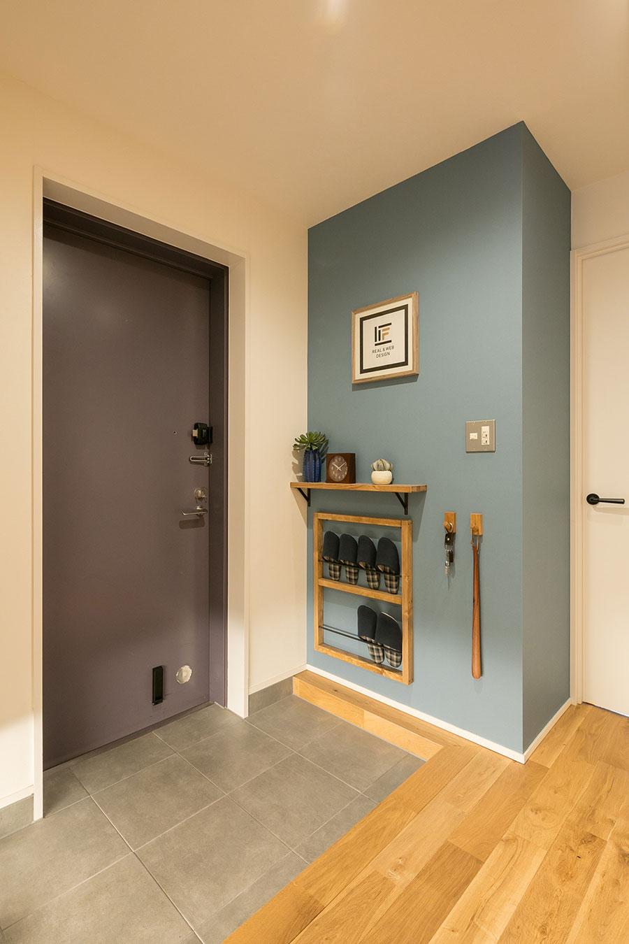 玄関の壁もくすんだブルーの壁紙を張った。棚やスリッパラックはマサヤさんがDIYで設置した。