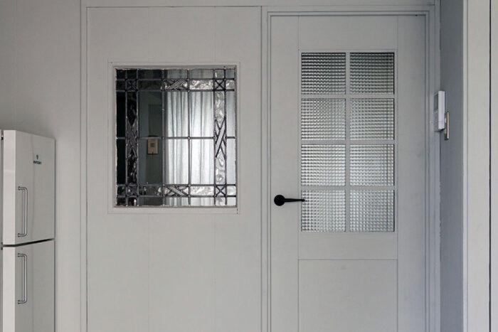 アンティークガラスの室内窓はもともと取り付けられていた。ドアは当初、木目だったものをグレーに塗装。バスルームからの光と、リビングからの光が室内で交差する。