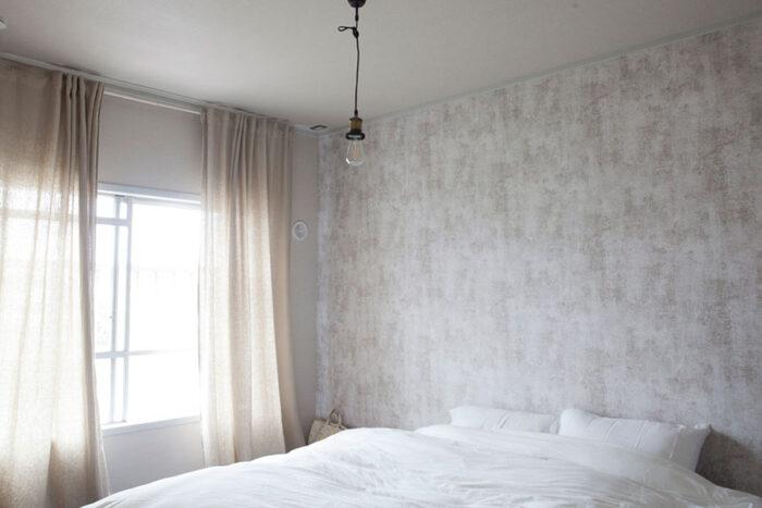 ベッドルームはベージュ系の壁紙とカーテンでコーディネート。カーテンレールは天井下ぎりぎりに移動させた。