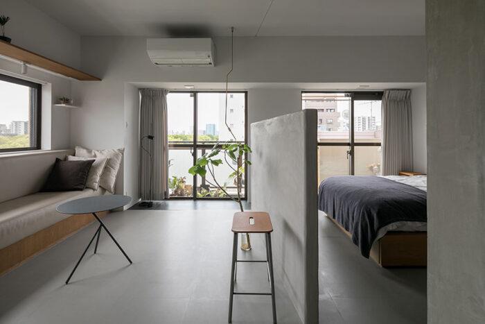 空間の広がりはそのままに、ベッドルームとリビングを低い壁で分けるアイディア。