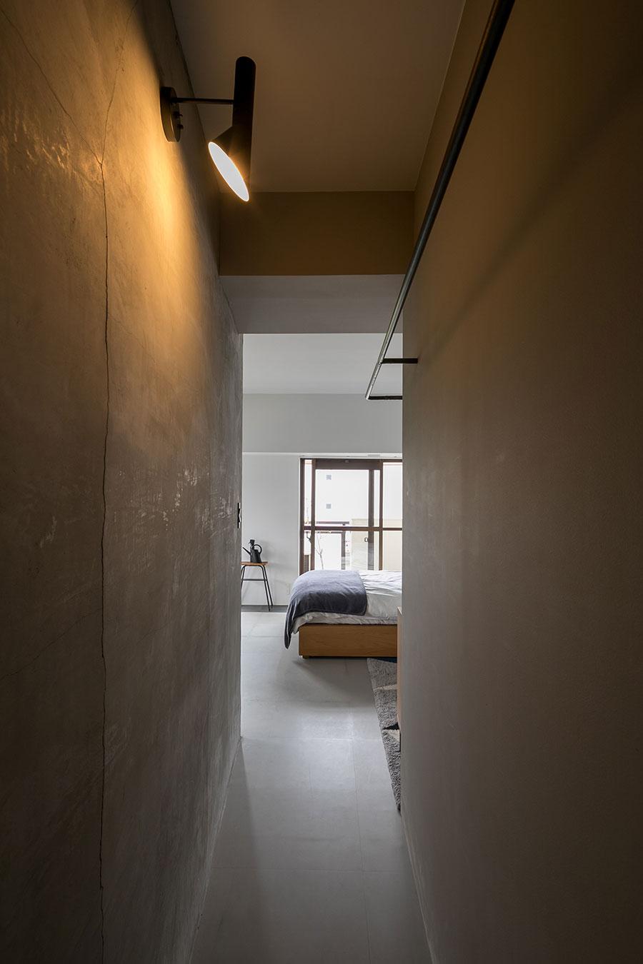 斜めの壁の裏側を通ってグルリと回遊できる。右側が浴室。ブラケットライトはアルネ・ヤコブセン。