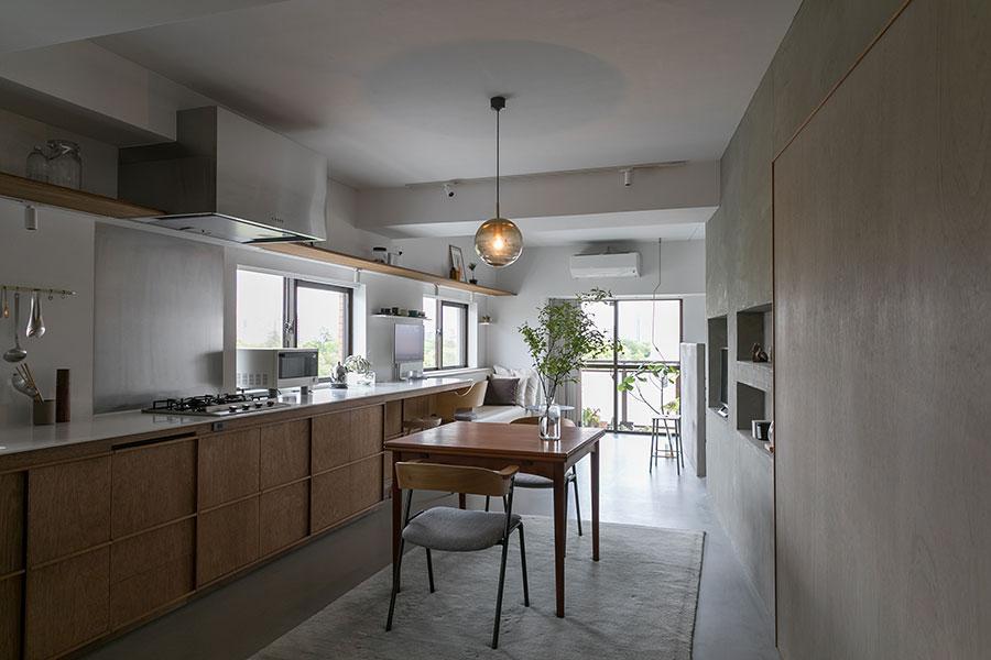 キッチンからワークデスクまで人工大理石の天板が連続する。ペンダントライトは、NEW LIGHT POTTERY。