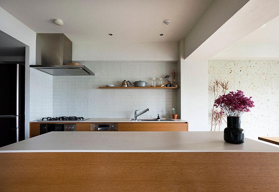 家具のように仕上げたキッチン。収納としても役立っている対面カウンターの天板は、セラミックで作業もしやすい。壁には薄いグリーン系のタイルを。