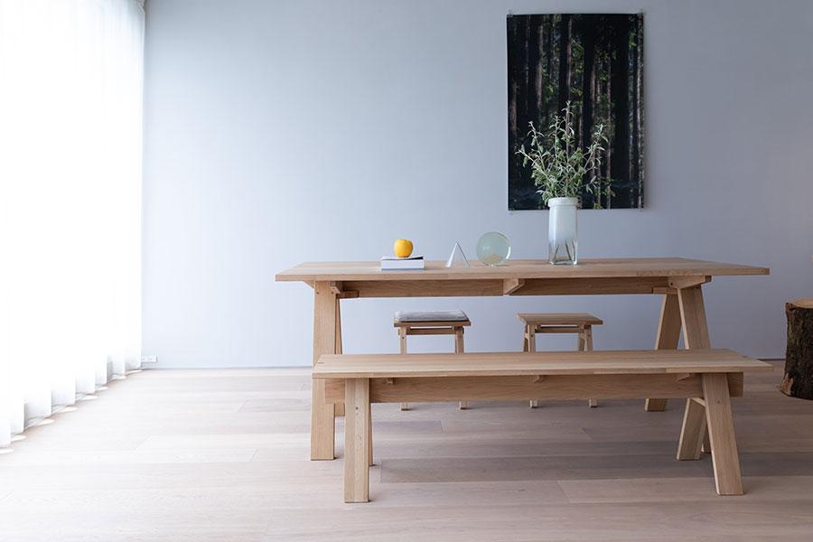 『石巻工房』のテーブルとベンチをカリモクが作った。集成材の天板は小口をそのまま残して素朴な仕上りに。