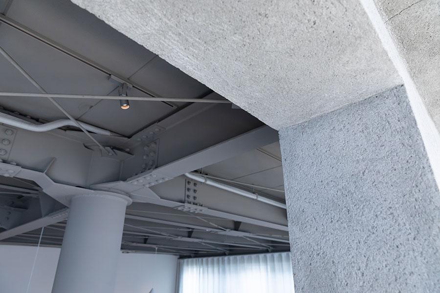 """3階は他のフロアよりも濃いグレーの壁。この色の違いで印象がガラリと変わる。手前は左官技術のひとつである""""掻き落とし""""で仕上げた、ラフな印象の壁。"""
