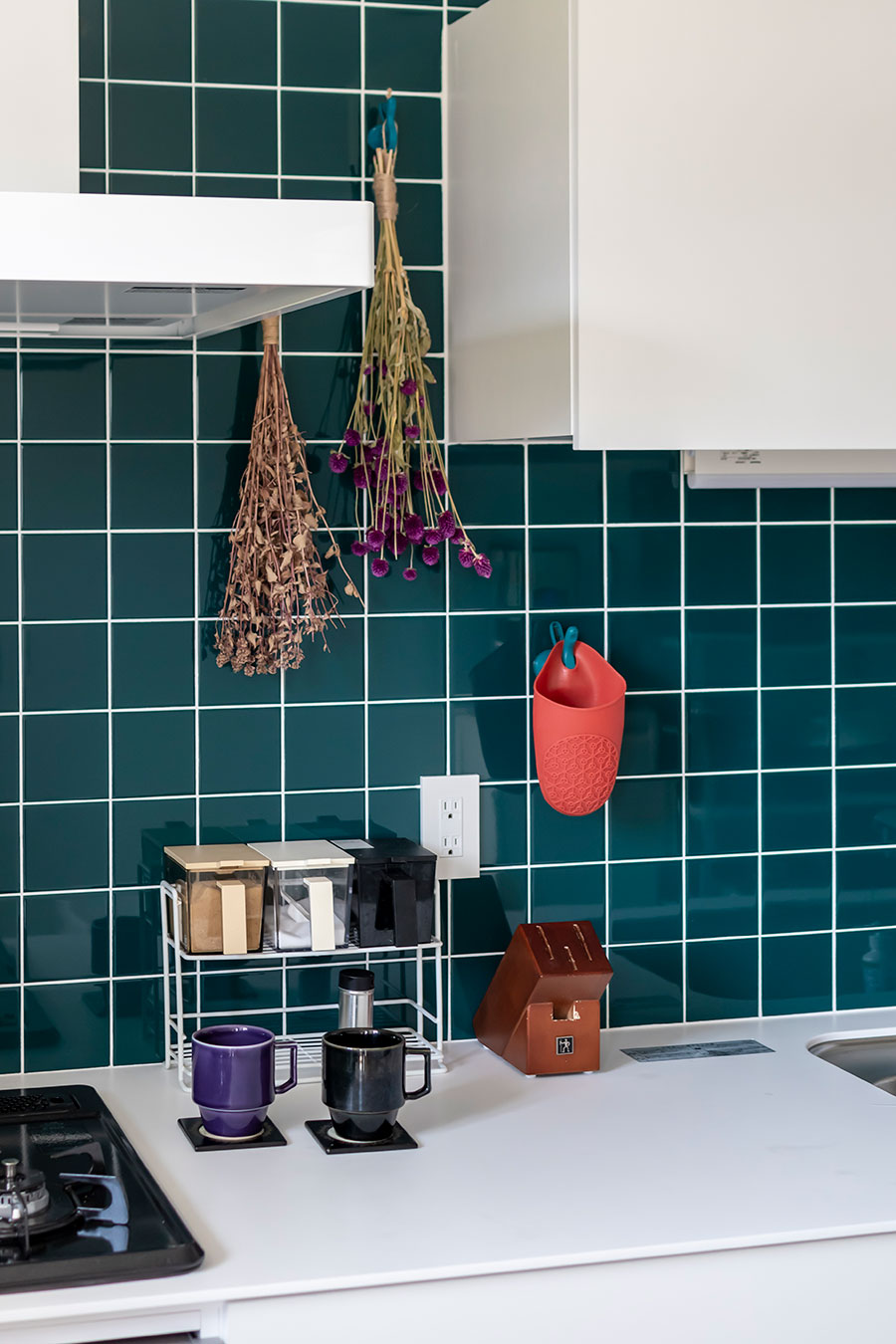 キッチン壁面はピーコックグリーンのタイルで上品な印象に。