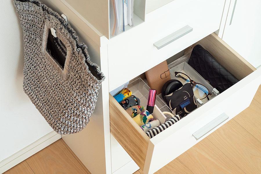 バッグは棚の横にかけ、中身を引出しに収納。小分けケースを使って整然と管理。