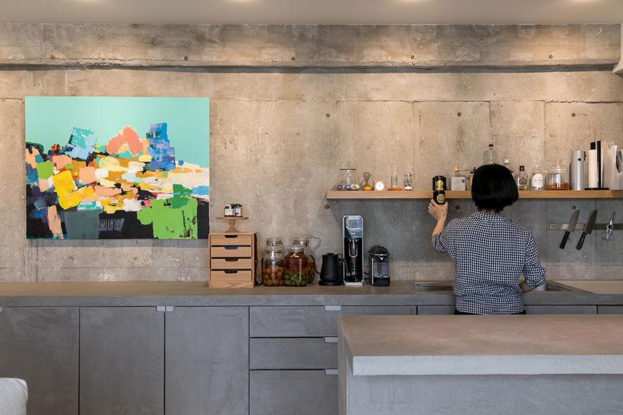 キッチンは防水性の高いモールテックス、壁はコンクリート現し。床は一段下げている。「アイランド型のカウンターテーブルを使ってお菓子作りも楽しみます」と亜季さん。コンクリートの壁に映える左のアートは、台湾に出張した際に譲り受けたものだそう。