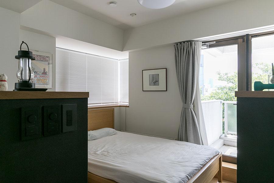 ベッドルームの床は一段下げ、リビング側からの存在感を消している。