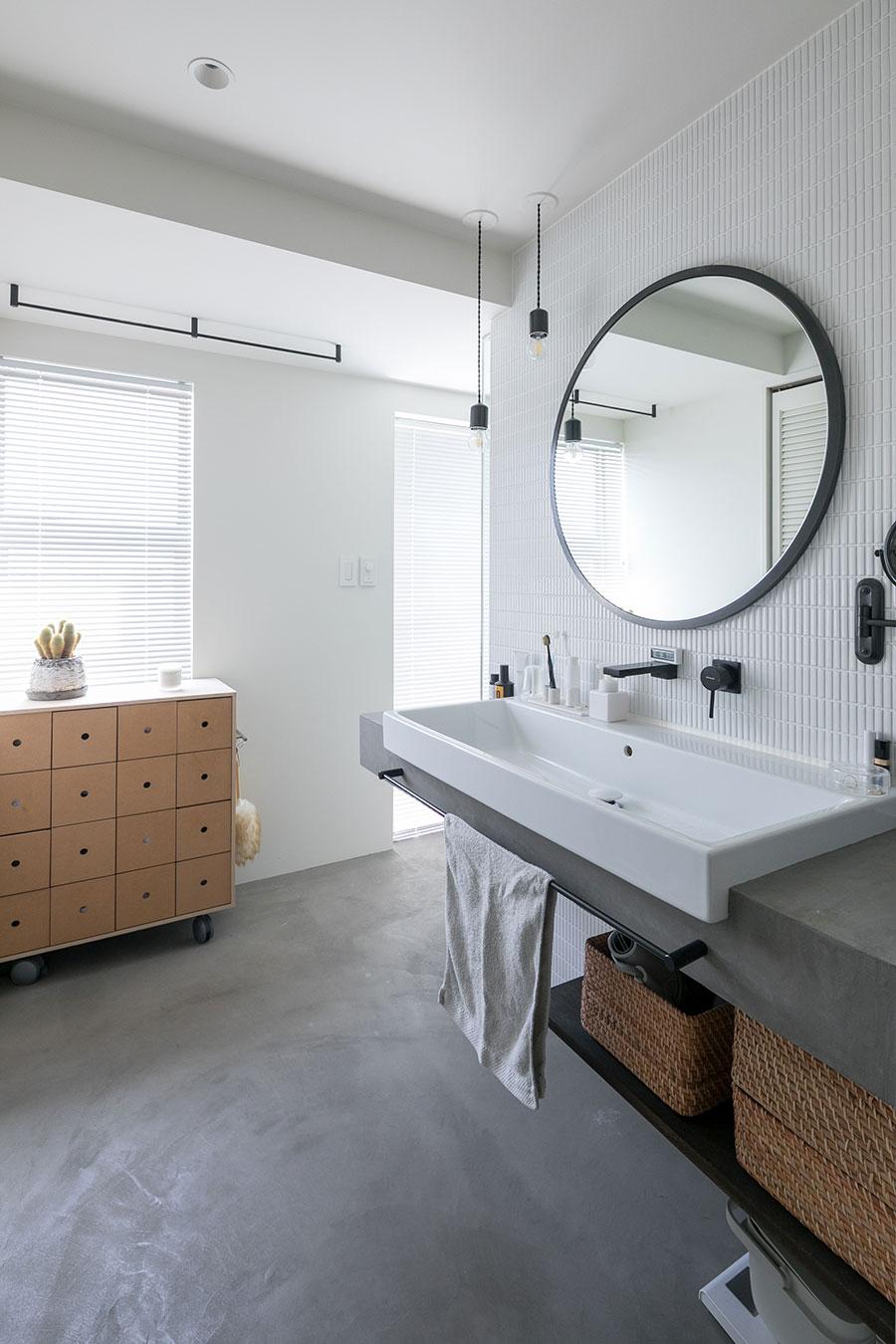 こだわりの洗面室。黒の蛇口や鏡のフレームが空間をキキリと引き締める。