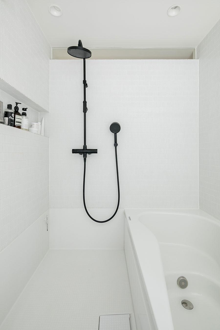 白の空間に黒のレインシャワーとシャワーヘッドがクールなハーフユニットバス。「夫はレインシャワー派、私はハンドシャワーをよく使います」