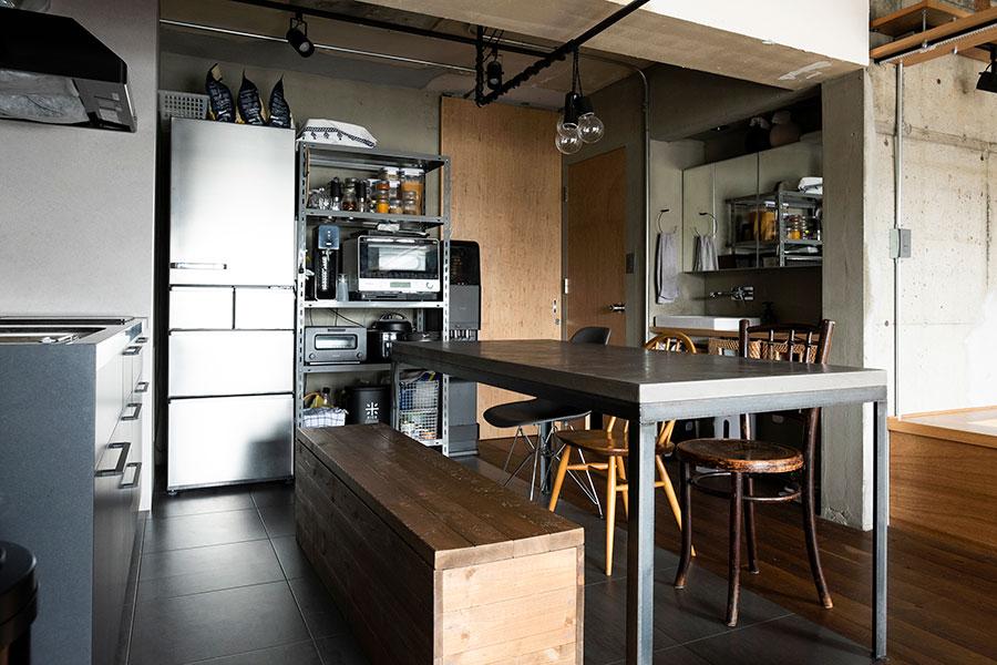 躯体現しのクールな空間に調和するキッチン。イスはアーコールや、50年代のチャーチチェアなどをメルカリで探して購入したそう。手前の収納にもなっているベンチは、作家さんにオーダーしたもの。