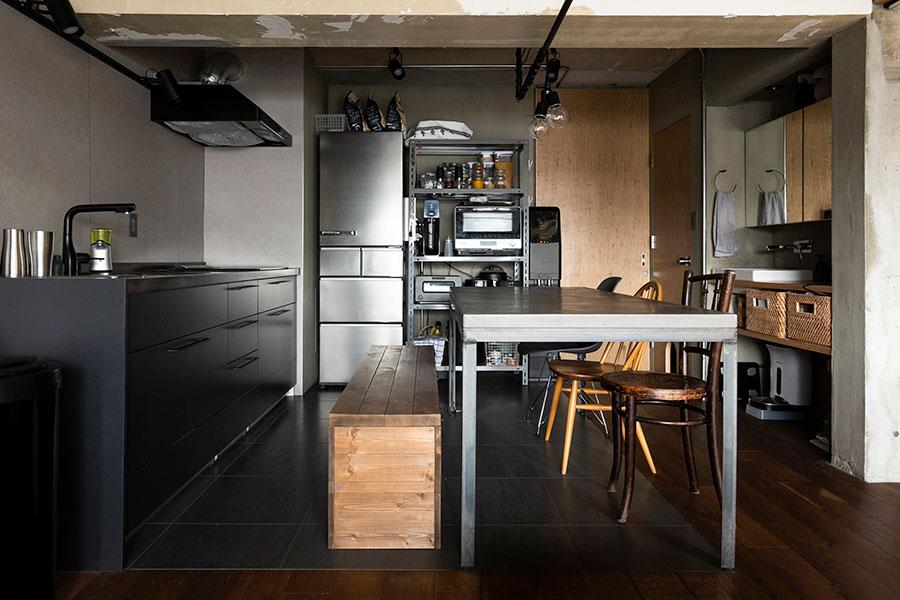 シ黒のキッチン台が空間を引き締める。床は汚れに強いPタイル。天井下まで占める大きなラワンの引き戸をリクエストした。