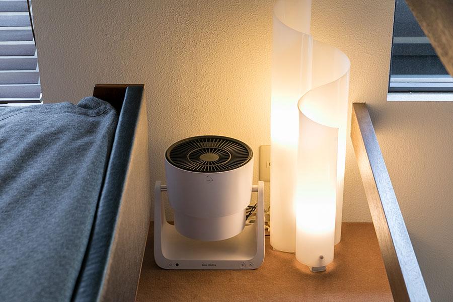 2階寝室の吹き抜けの横に、天井を向けて置いた『BALMUDA』のポータブルサーキュレーター。曲線が美しい照明器具とベッドの間に。