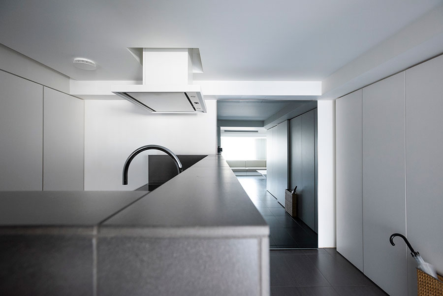 エントランスでもあるキッチンスペース。鏡の引き戸を閉じることで、LDKの一角に早変り。リビングに対して天井は低く設定され、変化がつけられている。