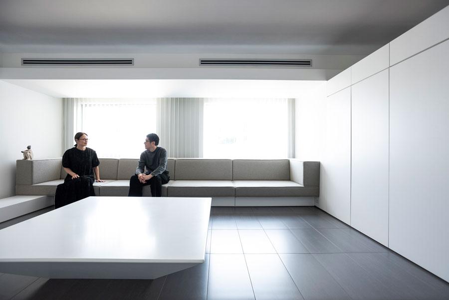真白の壁とグレーの床、薄グレーの天井に包まれた、究極的にシンプルでミニマルなリビングで。ソファー上の梁をあえてふかすなど、空間デザイン上の細かな計算がなされている。