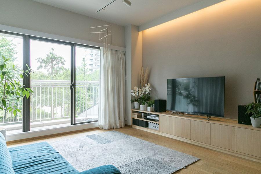 家族の集まるリビング空間。柱型を埋めるように造作のテレビボードを設置。壁面には間接照明を仕込み、心地よい明るさに。