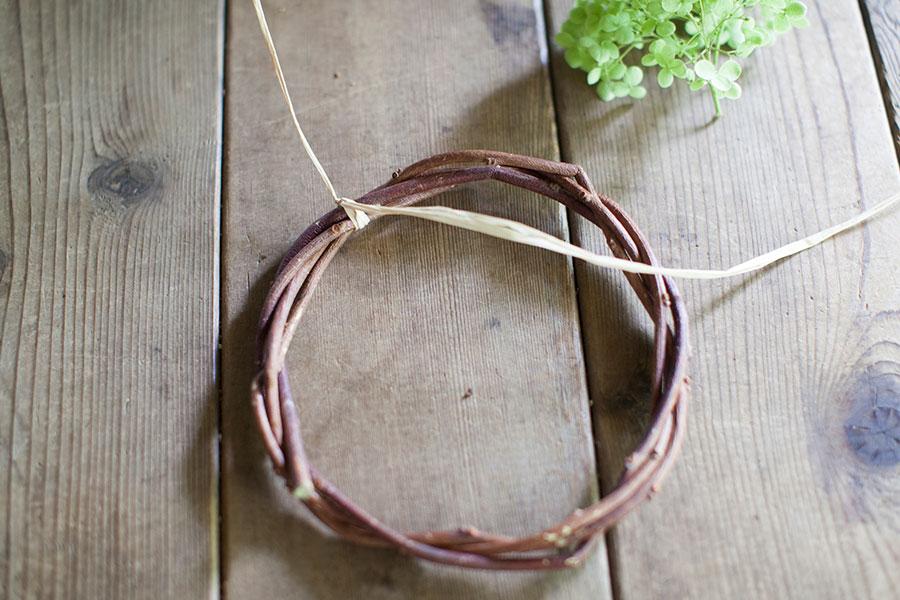 赤ヅルを2回巻いて直径15cm前後の輪をつくり、残りのツルをまわりにぐるぐるとしっかり絡める。ラフィアを片端10cm残して、輪に片結びする。