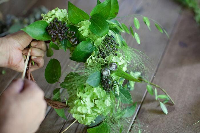 花材の配置は自由でOK。実ものに葉を添えるとかわいい雰囲気に。輪の真上に花材が載るよう注意しつつ、ツタやラフィアが見えないように埋めていく。