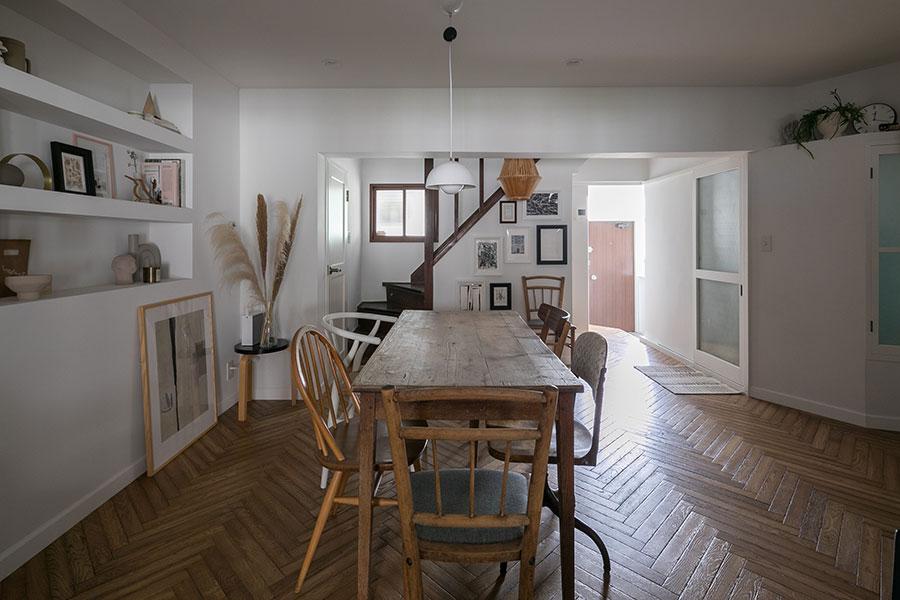 壁を取り払い大空間になった1階。床はアンティーク加工がされた材でヘリンボーン貼りに。テーブルは1920年代のフランスのアンティーク。
