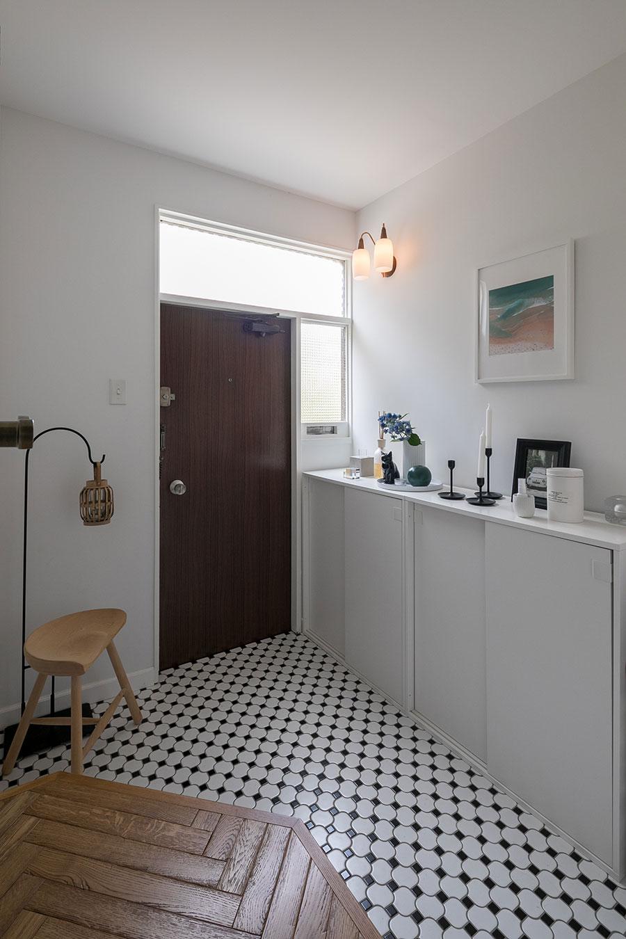 三和土部分を広げてゆったりつくり変えた玄関に、磨りガラスから柔らかな光が入る。白と黒のタイルがポップで楽しい印象。