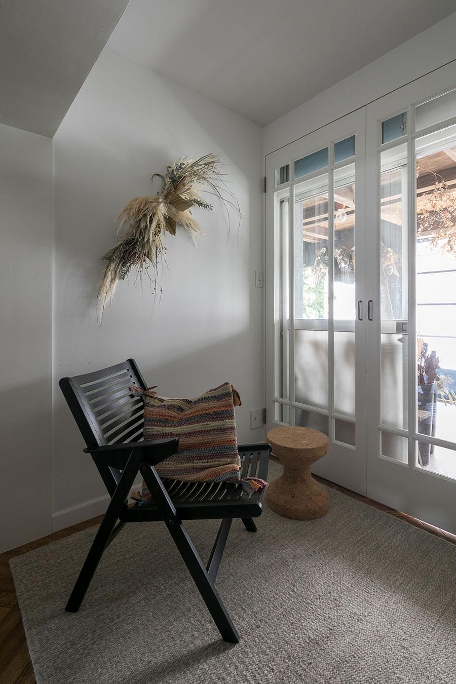 玄関と反対の南側の開口部。掃き出し窓の向こうは花屋で、その先は外につながる。壁面のドライフラワーアレンジメントはHarunaさんの作品。
