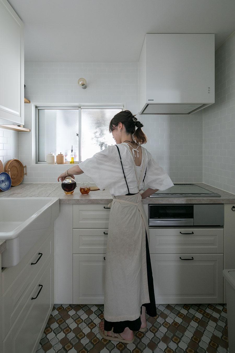 ご夫妻お気に入りのセミクローズドキッチン。ぴったり収まるL字ユニットがなくて、IKEAのI字ユニットを二つ組み合わせたそう。窓の向こうは花屋。