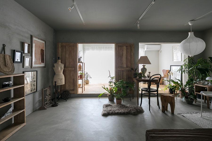 モルタル塗りが印象的な2階。手前側は元和室で、畳を外して一段下げた。「あったら可愛いと思って」つけた木製ドアは岡崎製材のもの。古色風のワックスを塗って味わいをプラスした。