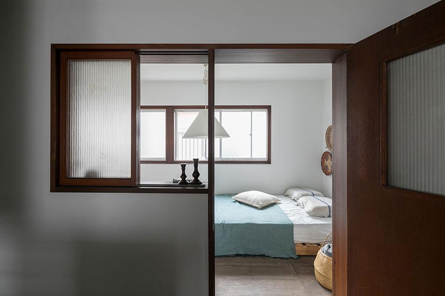 2階唯一の個室であるベッドルーム。木枠の窓が安らぎを醸し出す。床材にはステイン塗装をして、古色風に。