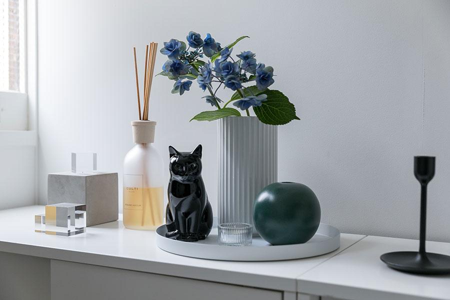 玄関のしつらえ。モダンな小物たちの中で黒猫やお花が生き生きと映える。