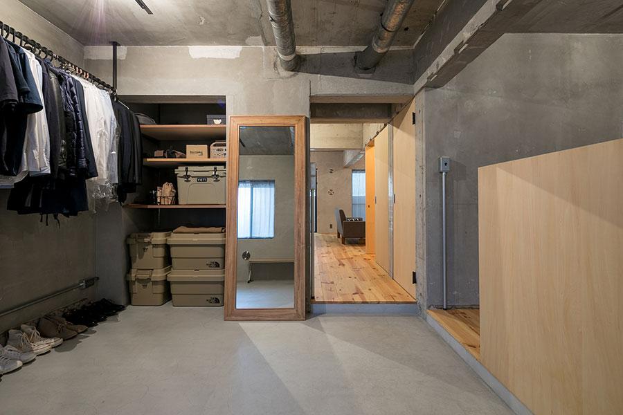 玄関入ってすぐの広々とした土間は、アウトドア用品の手入れにも便利に使える。収納としても使えるコンテナはサンドカラーで統一。「将来的に壁で仕切ることも想定し、コンセントの位置を工夫しました」