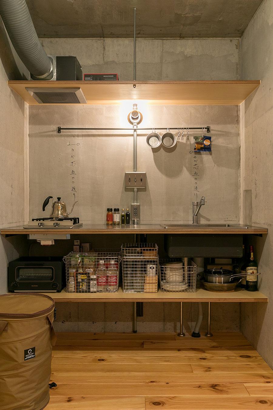 無印良品のスタッキングができるカゴを使い、きれいに整理整頓されたキッチン。ゴミ箱は、折りたたみできる筒型ケースの中。「キャンプに持っていって、同様にゴミ入れとして使っています」