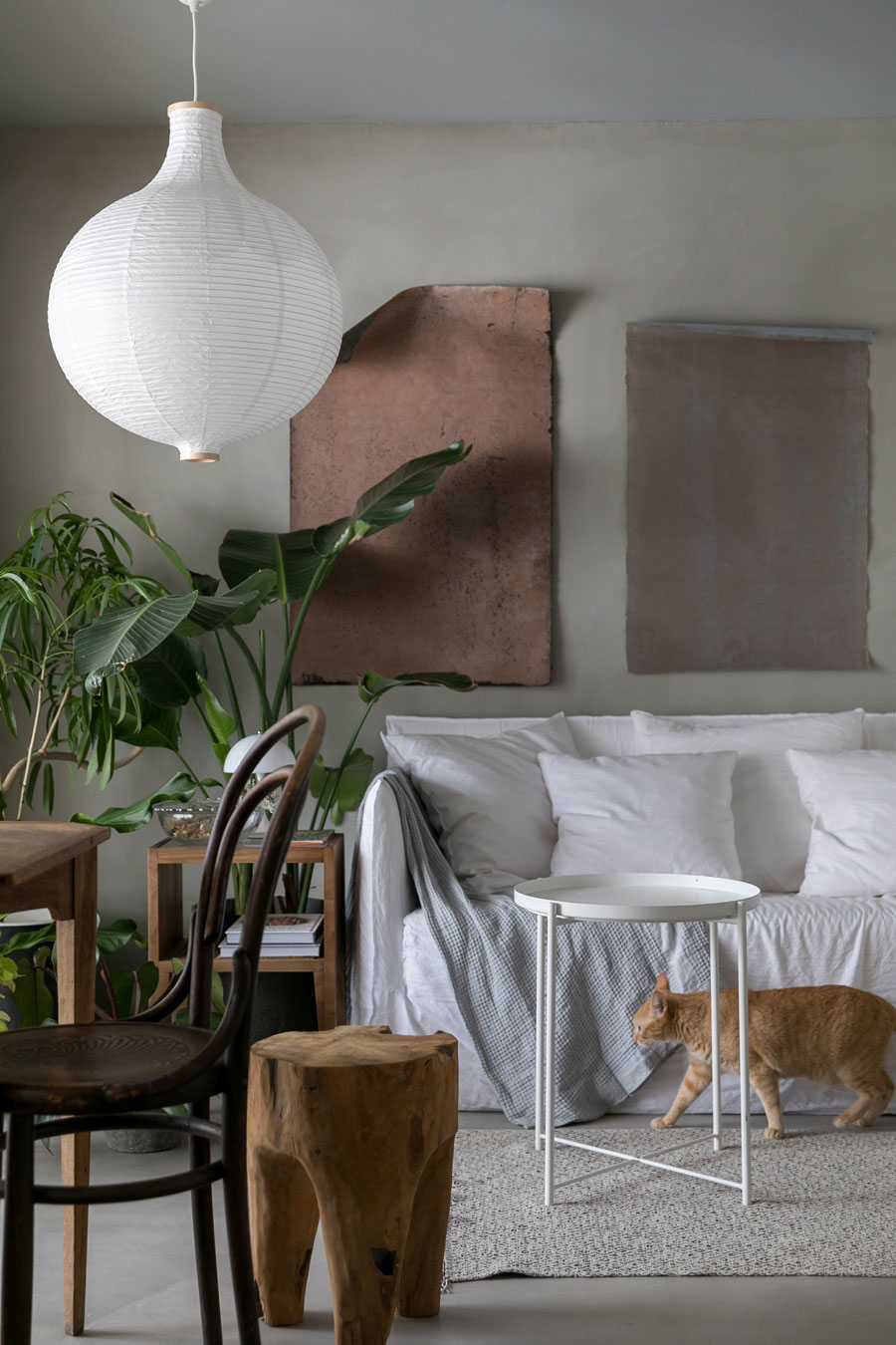 イタリアの高級家具ブランド「GERVASONI」のソファ、アイアン製のアート作品、「オルネ ド フォイユ」の切り株スツールなどが共演。白いテーブル、照明、ラグはIKEA。