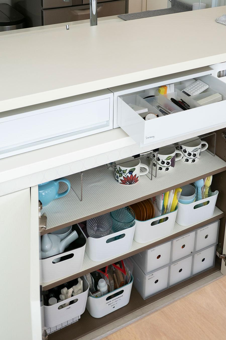 ダイニングに面したカウンターキッチン下の収納。来客用の食器を中心に収めている。上段には無印良品のポリプロピレンケース引出式を置き、引出し内を小分けのケースで仕切って文房具などを。