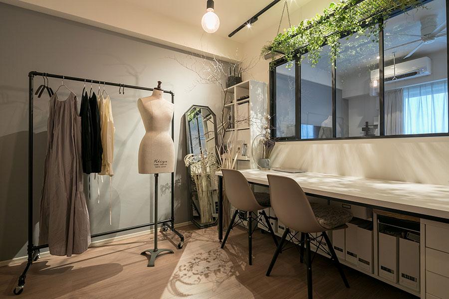 アトリエを入口から見る。ちさとさんがデザインするLiTAの服は、仕立ての良さと経年変化を楽しめる素材が好評で、ファン も多い。「家具は、造作にしない方がコストを下げられるとご提案いただき、既製品の組み合わせで構成していただきました」。デスクまわりは生地などのサンプル帳をすっきりと収納できるようになっている。