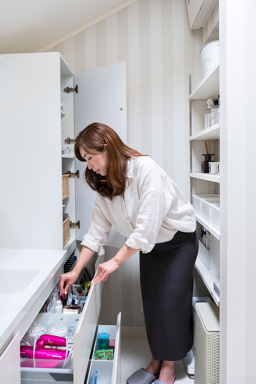 腰より低い位置の収納は、観音扉よりも引出し式が取り出しやすくて便利。ファイルボックスなどを使って、洗面台で必要なものを仕分けして収めている。奥の扉つきの棚には、タオルやお子さんのバスルームでの着替えセットを。背面には主に掃除用洗剤やグッズを、ディスプレイ感覚で収めている。