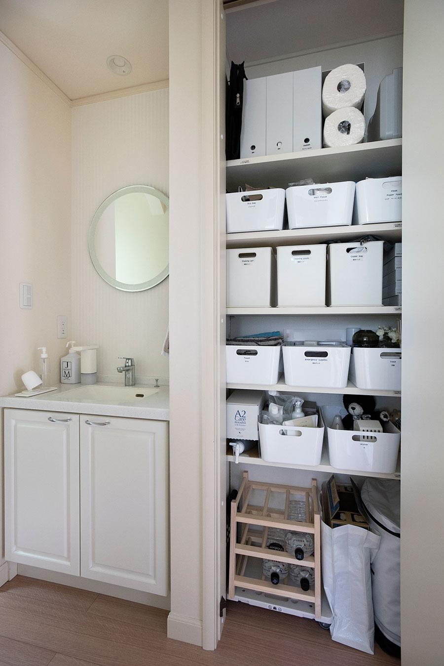 玄関付近にある洗面台の脇にも収納を。いちばん下にはキャスター付きの台を活用し、ミネラルウォーターをストック。